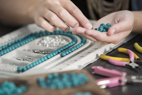 Close-up of woman working with beads to create a necklace - ZEF003637