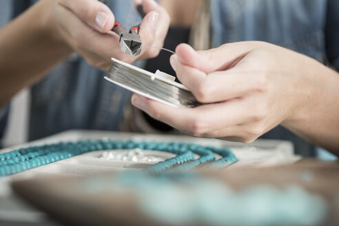 Close-up of woman working with pliers to create a bead necklace - ZEF003642