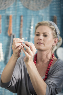 Woman working with wire to create a bead necklace - ZEF003653