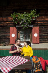 Austria, Altenmarkt-Zauchensee, young couple with beer glasses sitting in front of Alpine cabin - HHF005159
