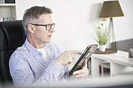 Businessman working with digital tablet at home office - SEGF000257