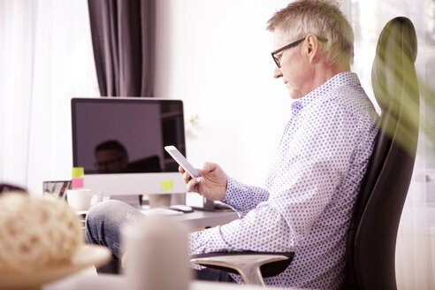 Businessman using smartphone at home office - SEGF000272