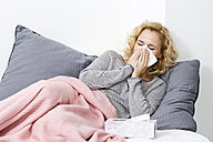 Sick woman lying on couch blowing her nose - MAEF009932