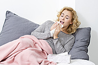 Sick woman lying on couch sneezing - MAEF009933