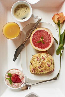Tray with homemade rhubarb scones, strawberry butter, grapefruit, fresh juice and coffee - HAWF000735
