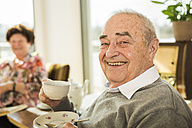 Portrait of senior man with cup of coffee at home - UUF003559