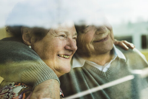 Happy senior couple head to head looking through window - UUF003571