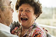 Laughing senior woman in the arms of her husband - UUF003579