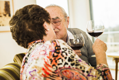 Kissing senior couple with glasses of red wine - UUF003581