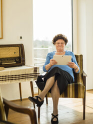 Portrait of senior woman using digital tablet at home - UUF003584