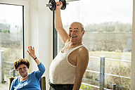Senior man with dumbbell at home - UUF003585