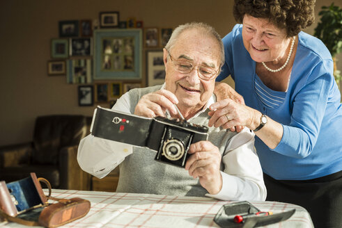 Senior couple with old camera at home - UUF003590