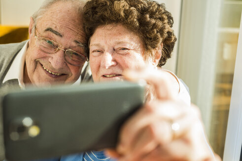 Senior couple taking a selfie with smartphone at home - UUF003592