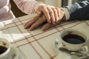 Senior couple holding hands at coffee break - UUF003595