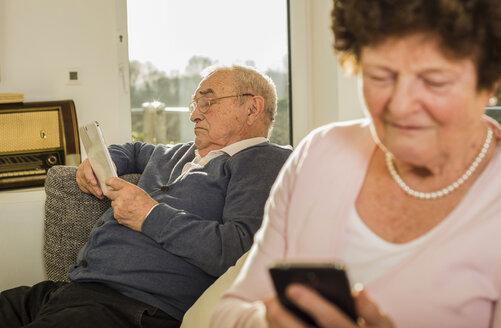 Senior man using digital tablet at home - UUF003609