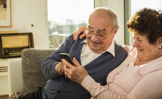 Senior couple using smartphone at home - UUF003610