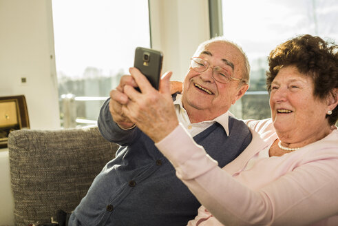 Senior couple taking a selfie with smartphone at home - UUF003611