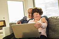 Senior couple using laptop at home - UUF003613