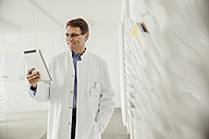 Smiling mature man in lab coat holding digital tablet - MFF001520