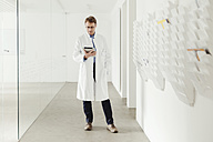 Mature man in lab coat standing in hallway looking at digital tablet - MFF001527