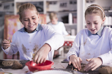 Two girls working on modeling clay in art class at school - ZEF005968