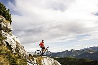 Austria, Altenmarkt-Zauchensee, young mountain biker looking at view at Low Tauern - HHF005293