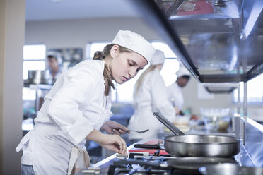 Teenage girl cooking in canteen kitchen - ZEF005948