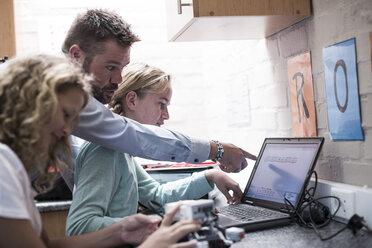 Teacher talking to schoolgirls with laptop in robotics class - ZEF006093