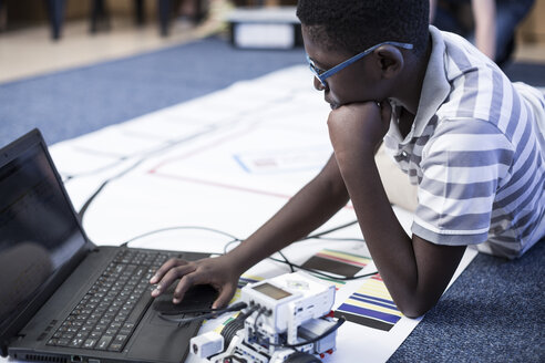 Schoolboy with laptop in robotics class testing vehicle on test track - ZEF006100