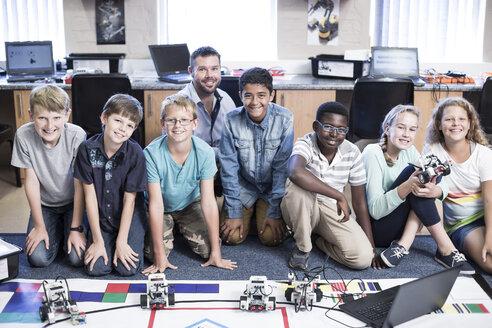 Portrait of smiling kids with teacher in robotics class - ZEF006104