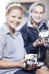 Two schoolgirls in robotics class presenting vehicles - ZEF006106