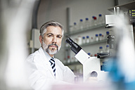 Portrait of scientist in laboratory with microscope - RBF002527