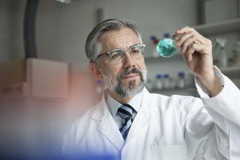 Scientist in laboratory examining liquid in round bottom flask - RBF002532