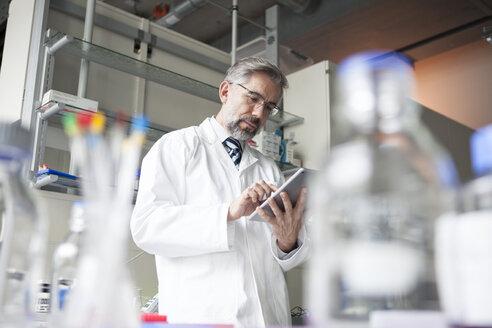 Scientist using digital tablet in laboratory - RBF002540