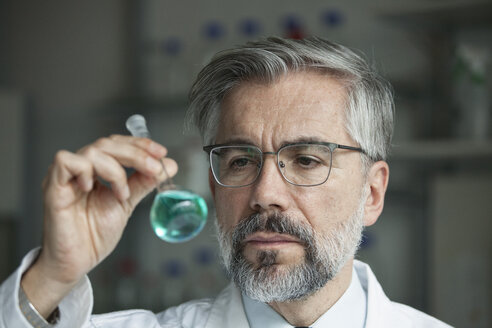 Scientist in laboratory examining liquid in round bottom flask - RBF002543