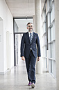 Confident businessman walking on hallway - RBF002559