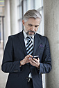 Businessman leaning against column using smartphone - RBF002560