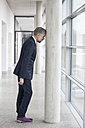 Frustrated businessman leaning against column - RBF002562