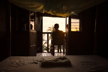 Philippines, Apo Island, man on the terrace of a wooden hut enjoying sunset - GEMF000128