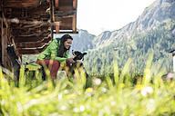 Austria, Altenmarkt-Zauchensee, young woman with dog at alpine cabin - HHF005169