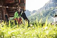 Austria, Altenmarkt-Zauchensee, young woman with dog at alpine cabin - HHF005170