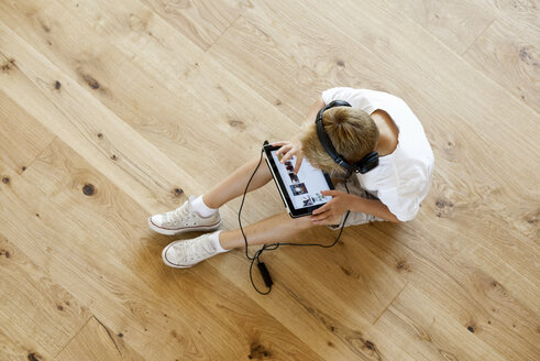 Boy sitting on wooden floor using digital tablet - LBF001081
