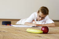 Boy doing homework on wooden floor with banana and apple in the foreground - LBF001084