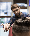 Hairdresser cutting young man's hair in a  barbershop - MGOF000164