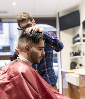 Hairdresser shaving young man's hair in a barbershop - MGOF000154