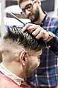 Hairdresser shaving young man's hair in a barbershop - MGOF000156