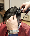 Hairdresser shaving young man's hair in a barbershop - MGOF000169