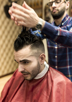 Hairdresser styling young man's hair in a barbershop - MGOF000150