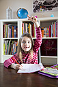 Girl doing homework raising her arm - SARF001564