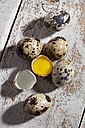 Whole and opened quail eggs on wood - CSF024996